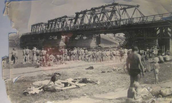 """Городской пляж 1960-х гг. Этот старый деревянный мост связывал город с Рабочим поселком и располагался ближе к сегодняшнему бассейну """"Юность"""". Мост был сожжен в 1970 году. Фото уникально тем, что, если внимательно присмотреться, можно заметить смельчака, прыгающего с самого верха деревянного ограждения (может и среди пользователей были такие смельчаки), хотя, это был довольно рискованный трюк и без несчастных случаев, к сожалению, не обходилось. Автор фото: Александр Паап.  Ухта"""